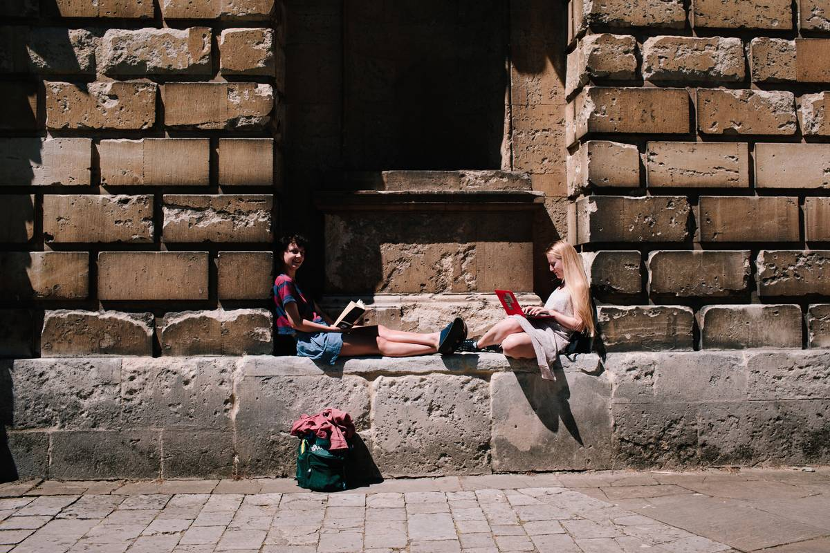 A pair of young women sit in an alcove of the outer wall of the University of Oxford.