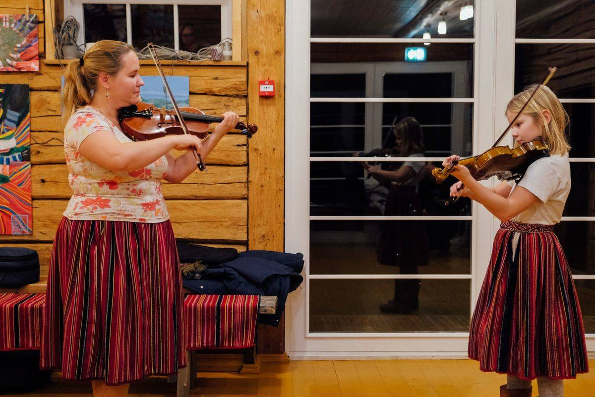 An Estonian teacher instructs a girl on violin playing.