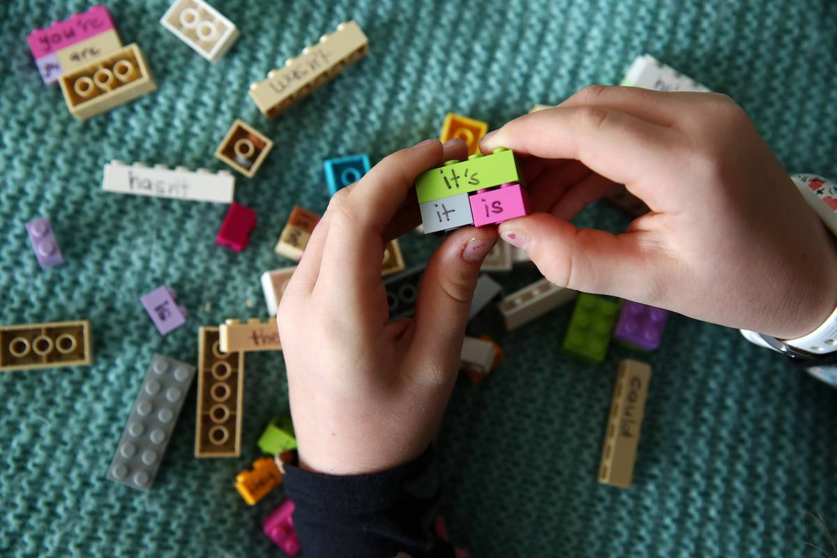 A student in New Zealand puts together legos to learn English grammar.