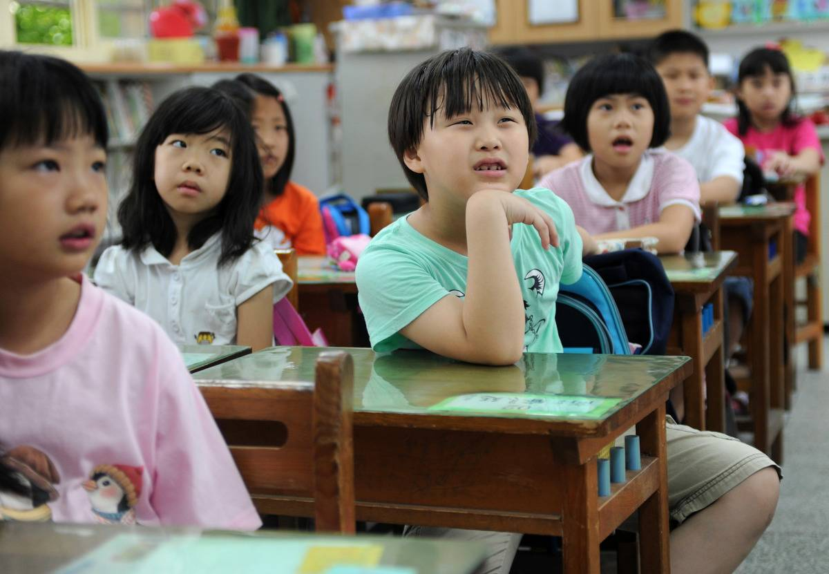 Elementary school students pay attention to the teacher in a Taiwanese classroom.