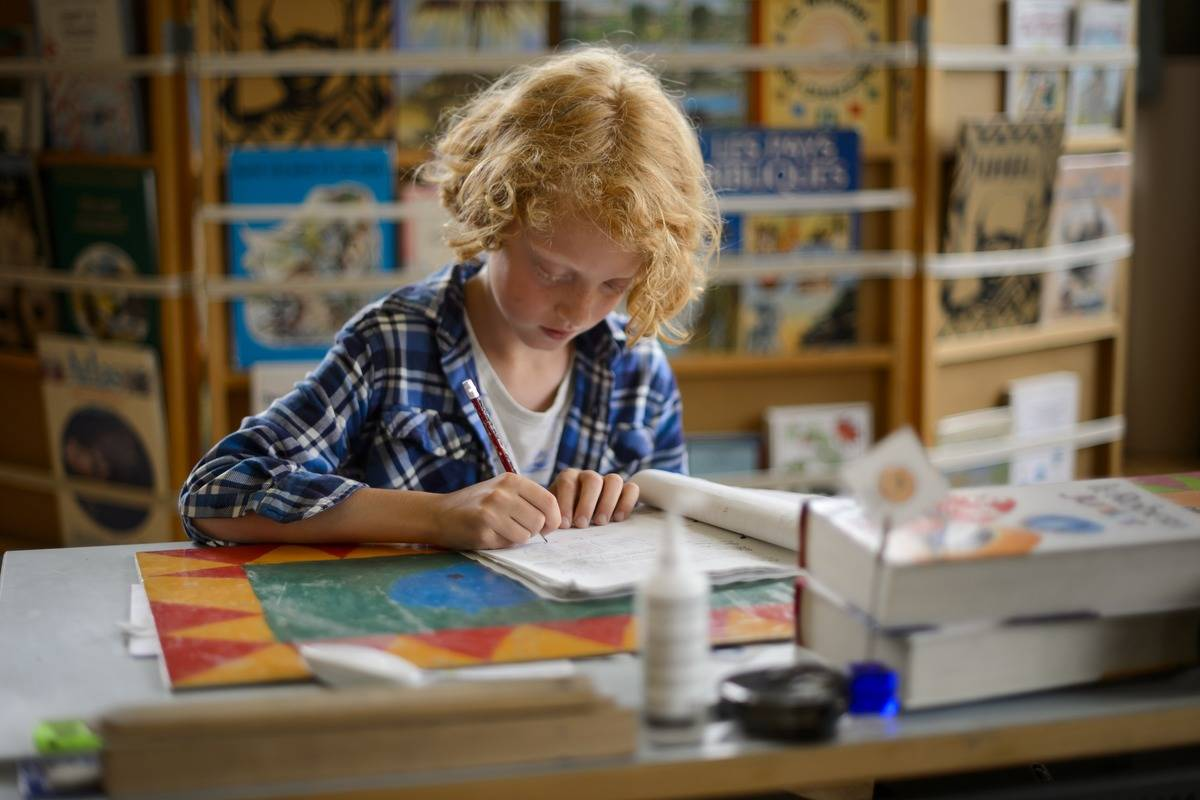 A nine-year-old Switz student works at his classroom desk.