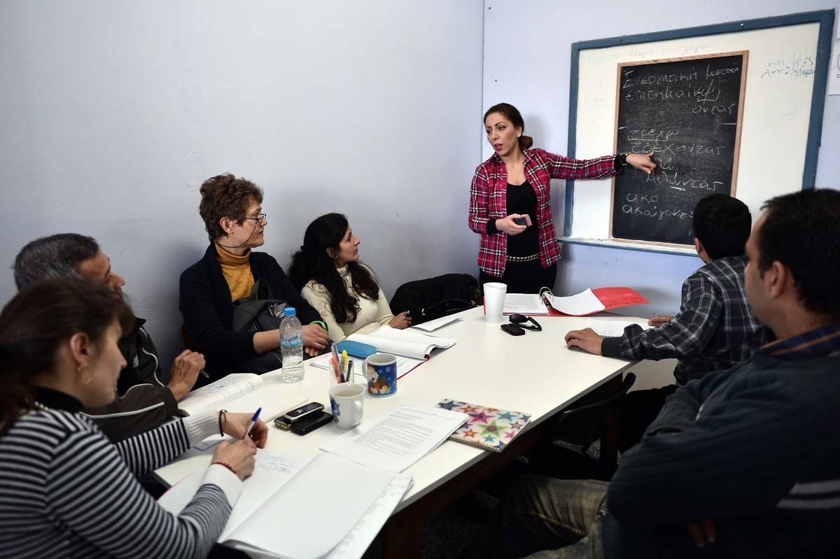 A volunteer teaches Greek lessons to immigrants.
