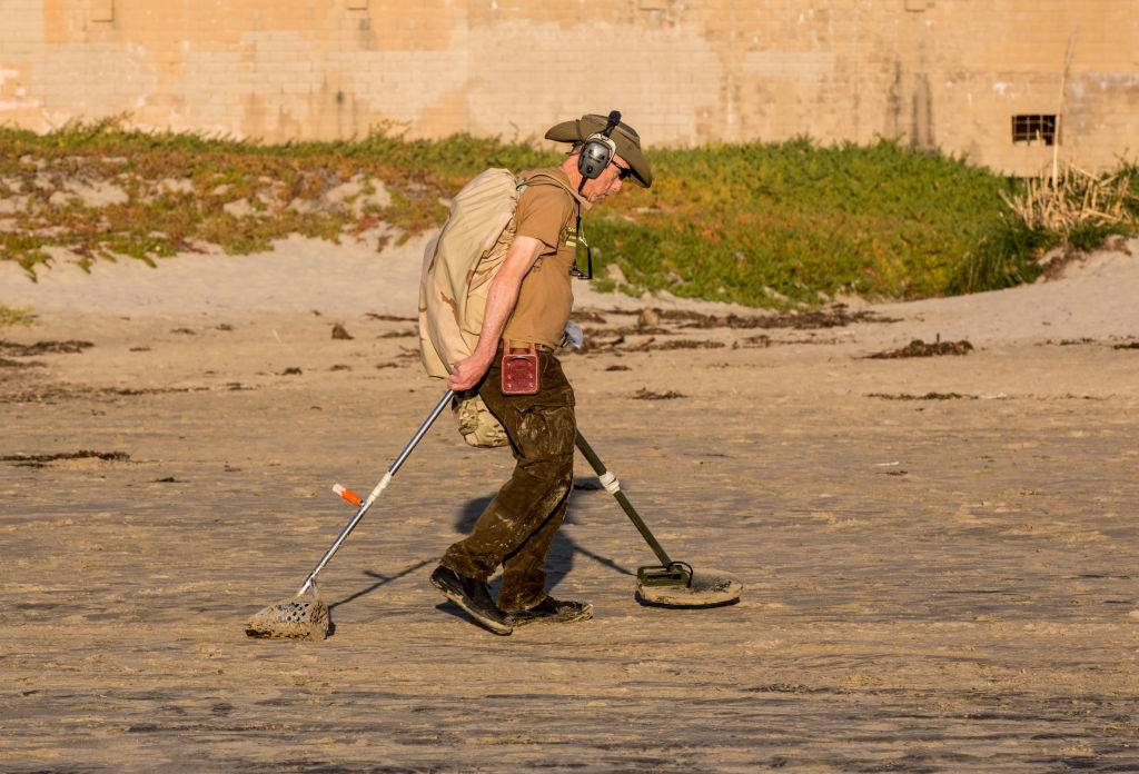 A man searches the beach with a metal detector