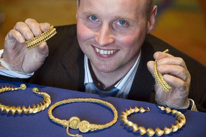 Amateur treasure hunter David Booth poses at the National Museum of Scotland in Edinburgh on November 5, 2009 with the Iron Age gold neck ornaments (torcs), dating circa from 300-100 BC, he found in September 2009 with a metal detector in a field near Stirlin
