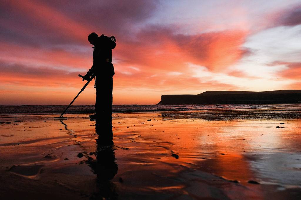 A detectorist sweeps the sand on the beach with his metal detector as clouds light up