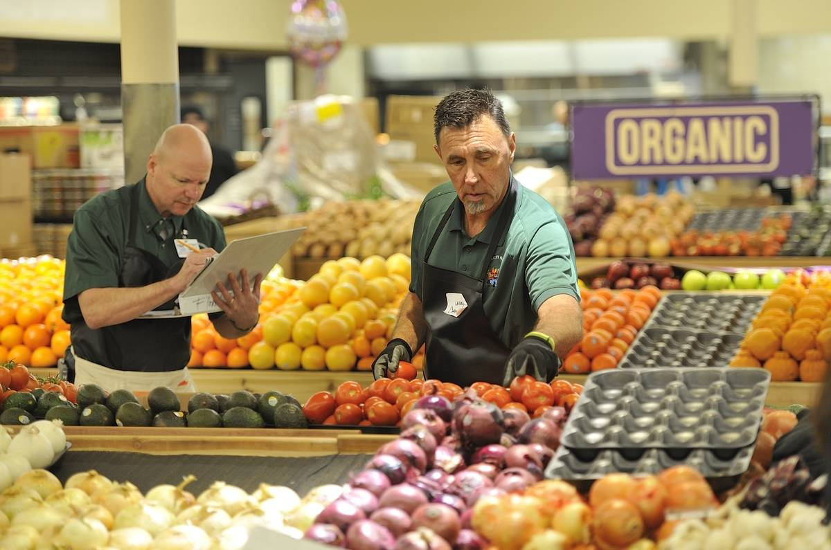 Two employees keep track of produce in a Laguna Beach Albertson's.