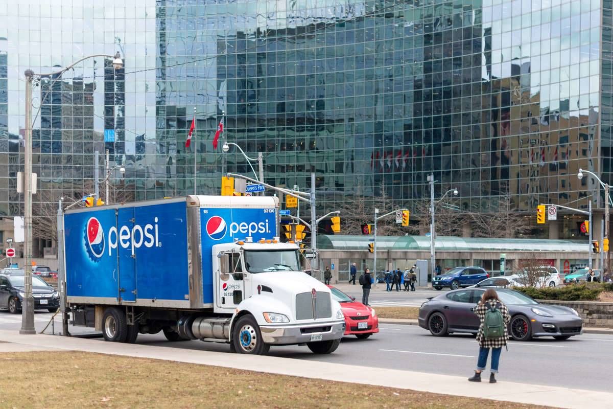 A large Pepsi Cola truck is parked in an intersection.