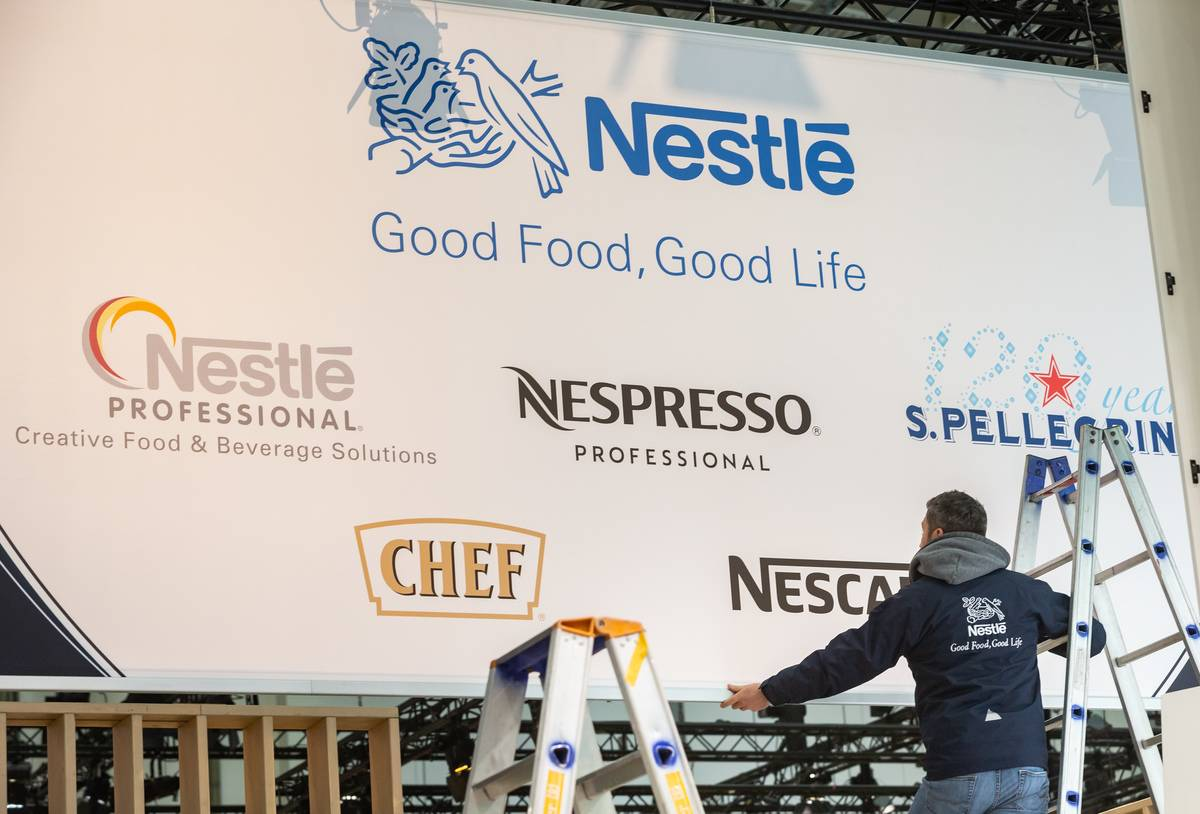 A man works on a billboard of Nestlé and the companies that it owns.