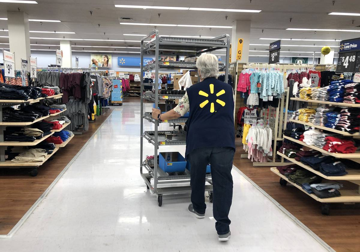 A Walmart employee pushes a cart through the store to restock shelves.