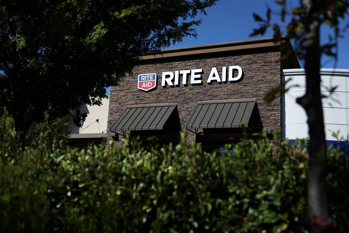 A Rite Aid store is seen through the trees.