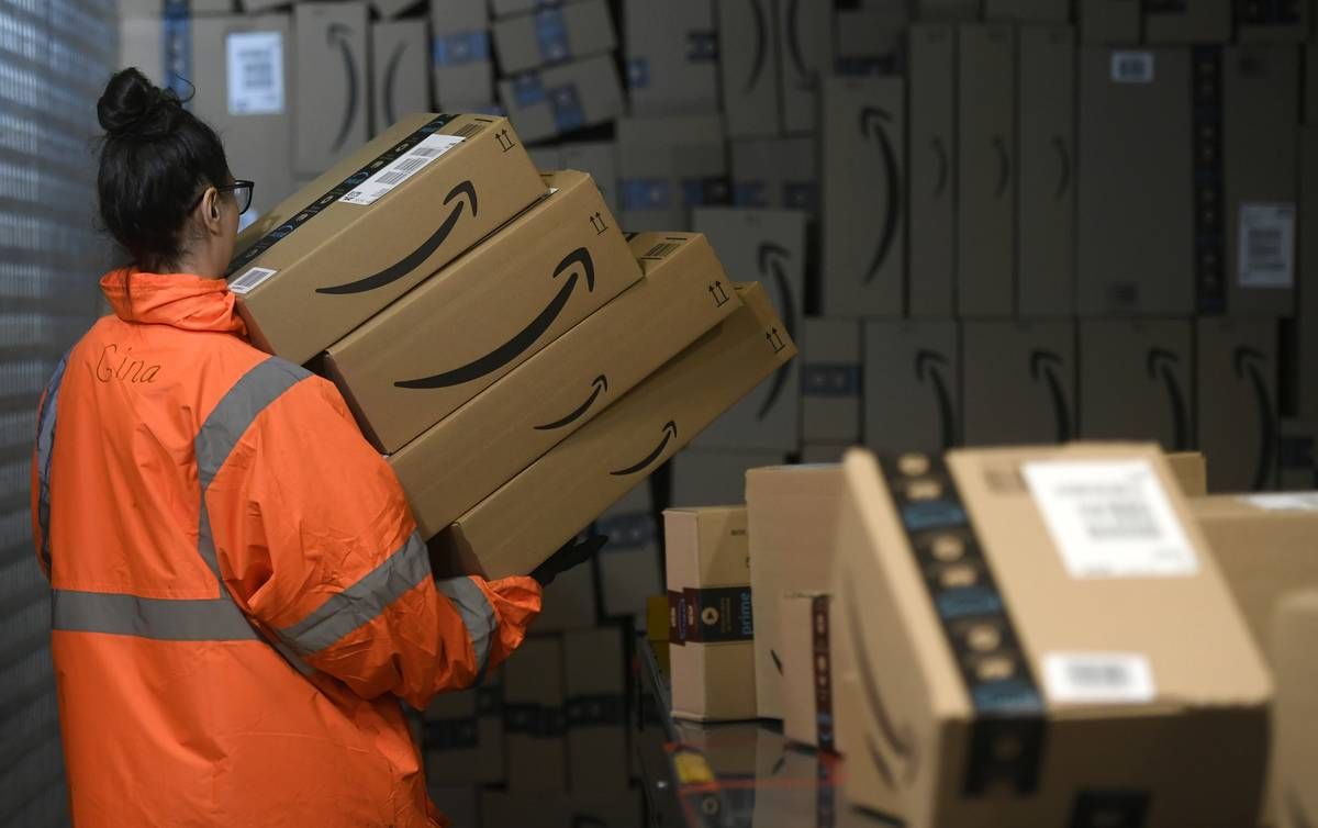 An Amazon employee carries packed goods at the distribution center.