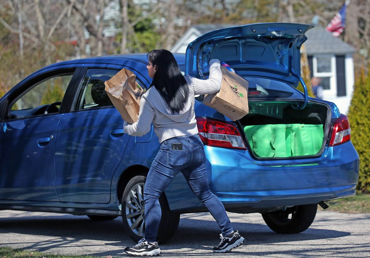 An Instacart shopper removes bags from her car to deliver to a customer's home.