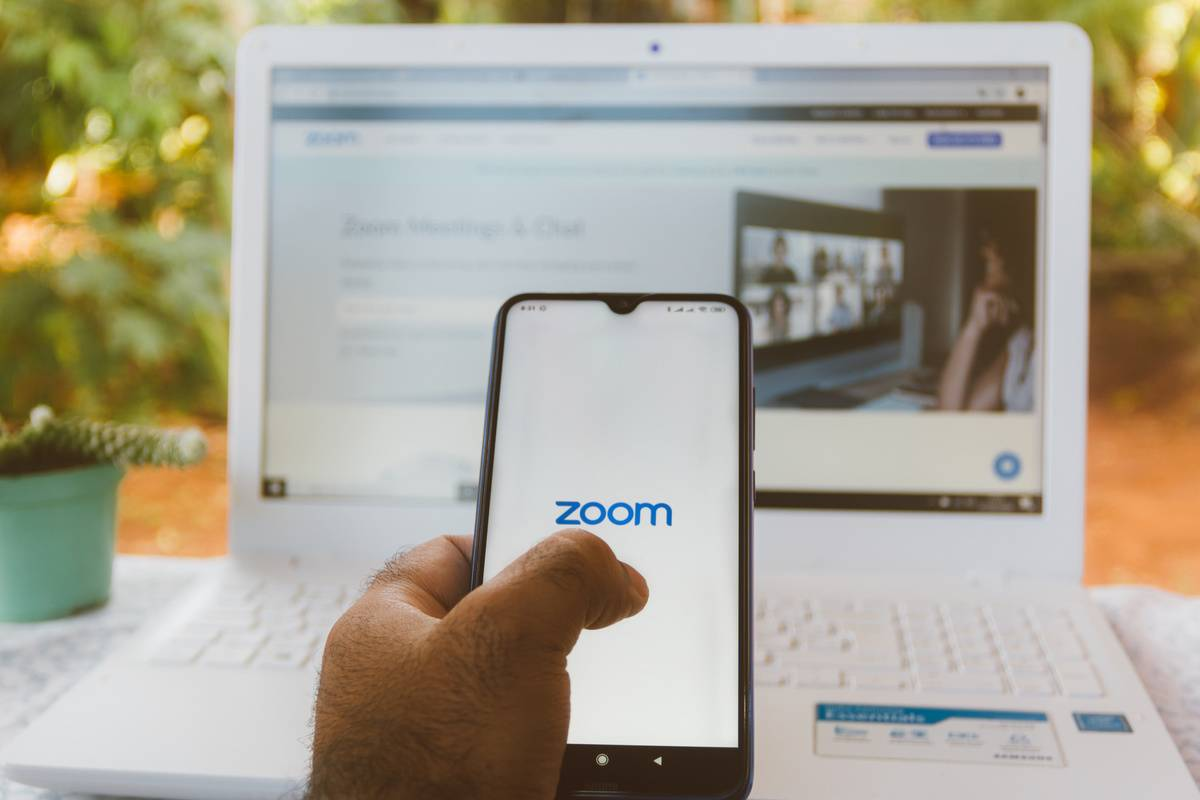 A person logs onto the Zoom app on their phone in front of their laptop.