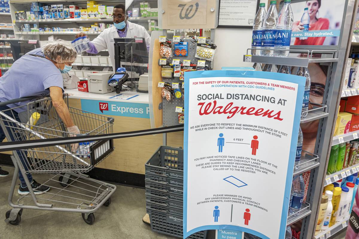 A sign about social distancing is erected in a Walgreens pharmacy.