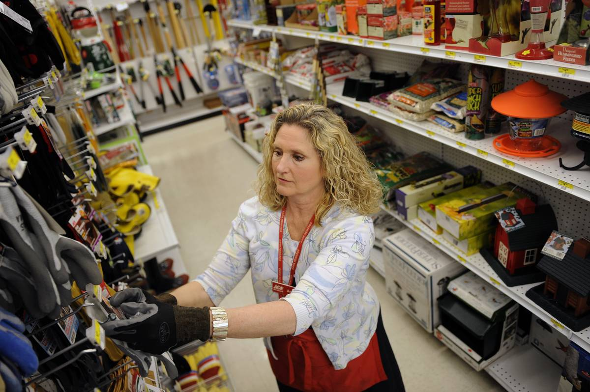 ACE Hardware owner Ann Bevans Cummiskey stocks the store before it opens.