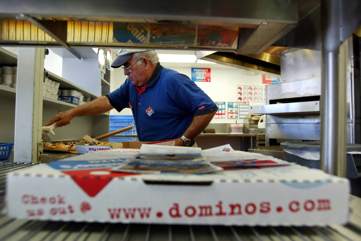 A Domino's employee is seen in the kitchen behind a pizza box.