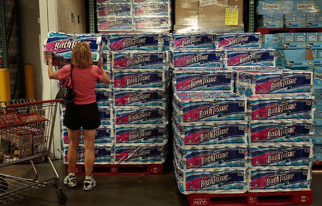 A shopper grabs a bulk package of toilet paper