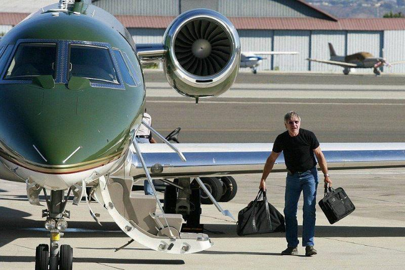 Harrison Ford leads his private jet with luggage.