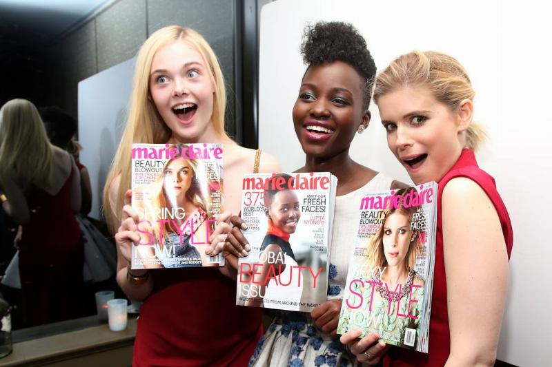 Actors hold up copies of Marie Claire magazine that they were on the cover of.