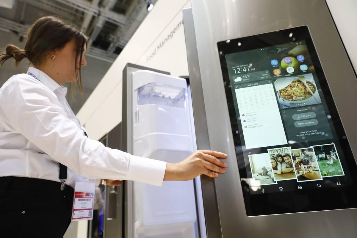 A woman opens a smart refrigerator.
