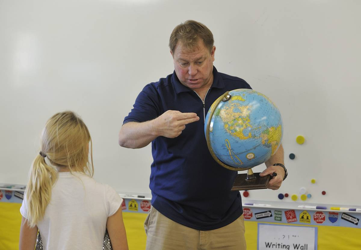A teacher points to a globe while talking to a student.