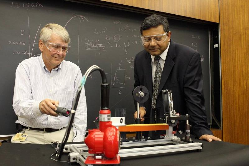 Two instructors demonstrate a scientific tool.