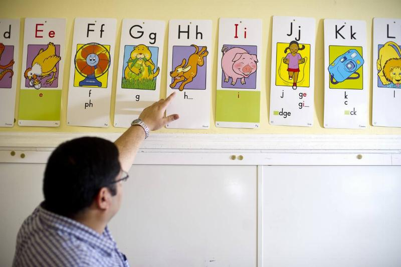 A teacher in Connecticut points to a letter in the alphabet.