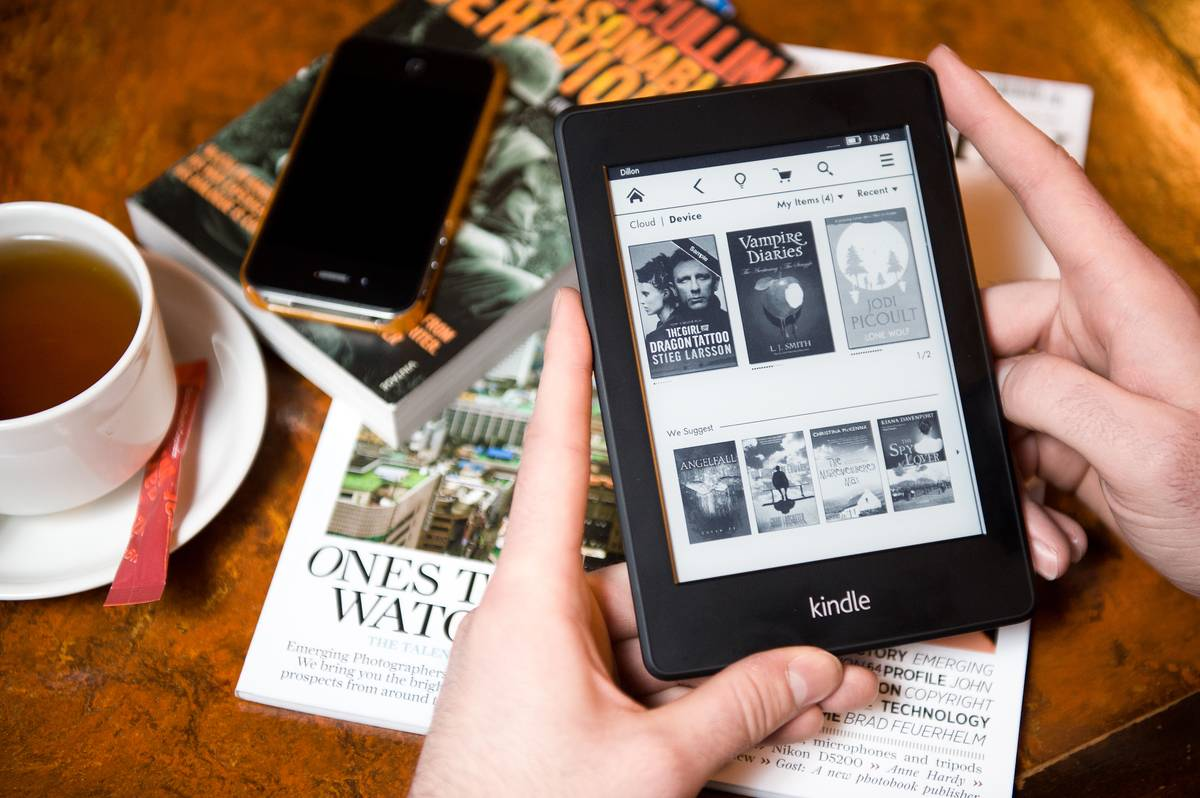 A person reads a Kindle Paperwhite at a cafe.