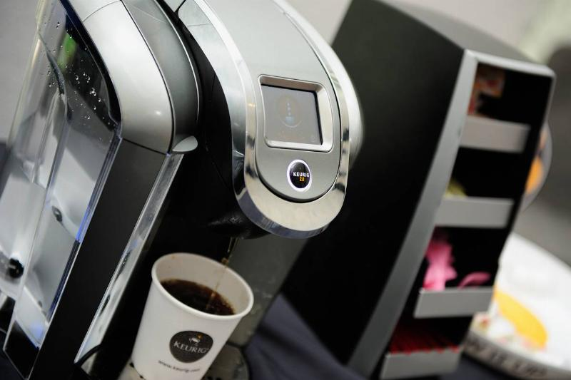 A Keurig machine brews coffee.