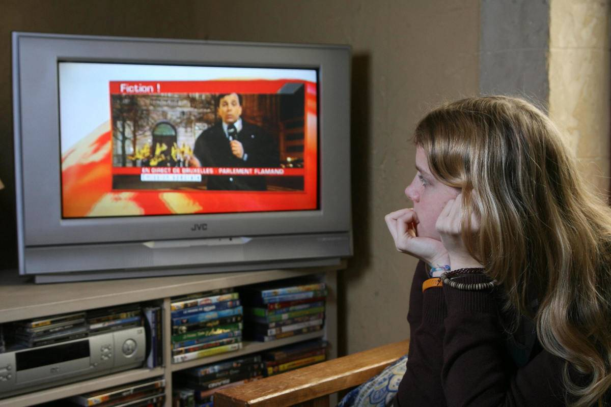 A teenage girl watches the news on TV.