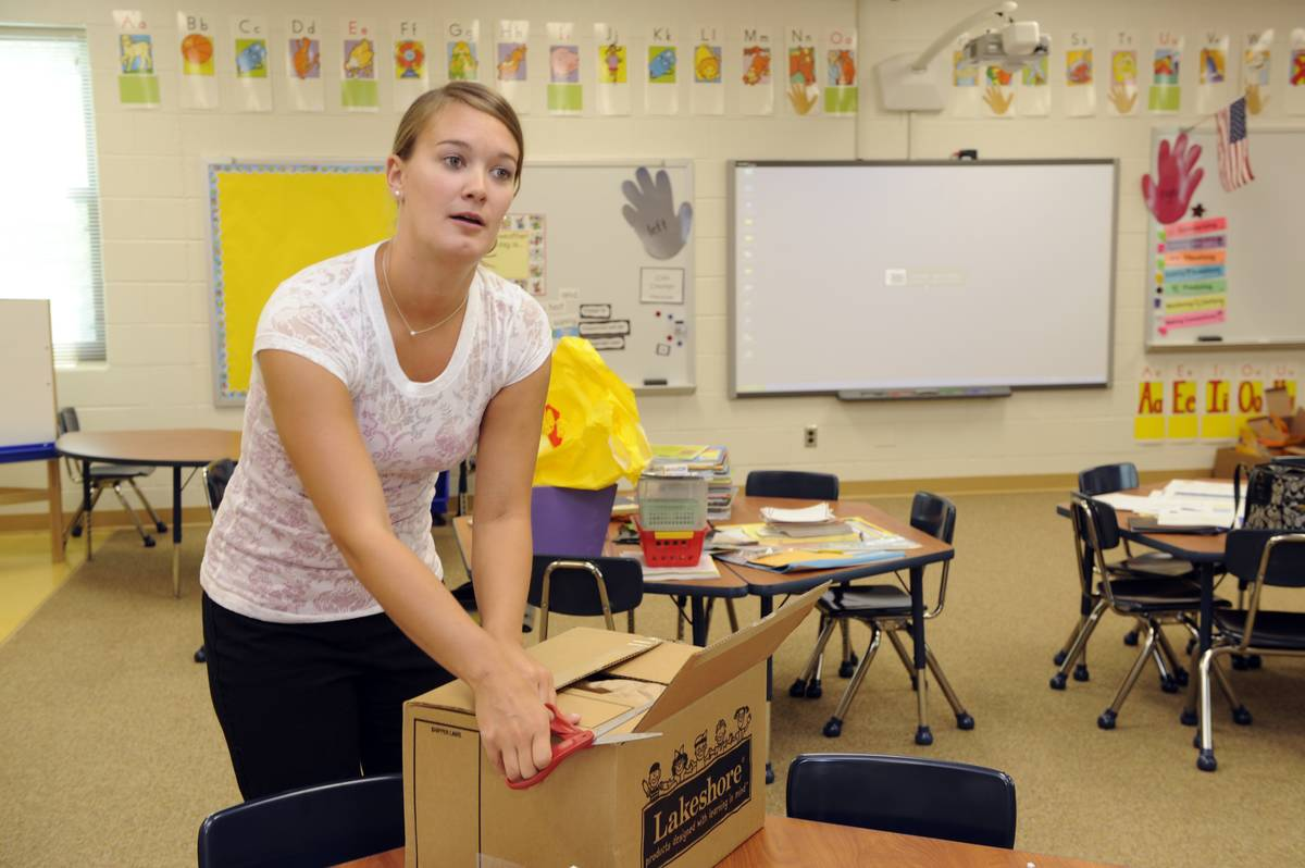 A Maryland teacher opens a package of school supplies in her classroom.