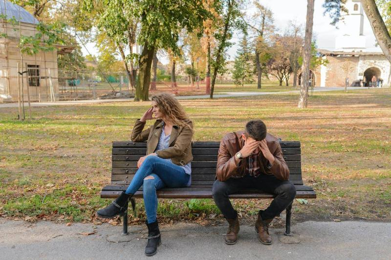 couple in fight while sitting on park bench