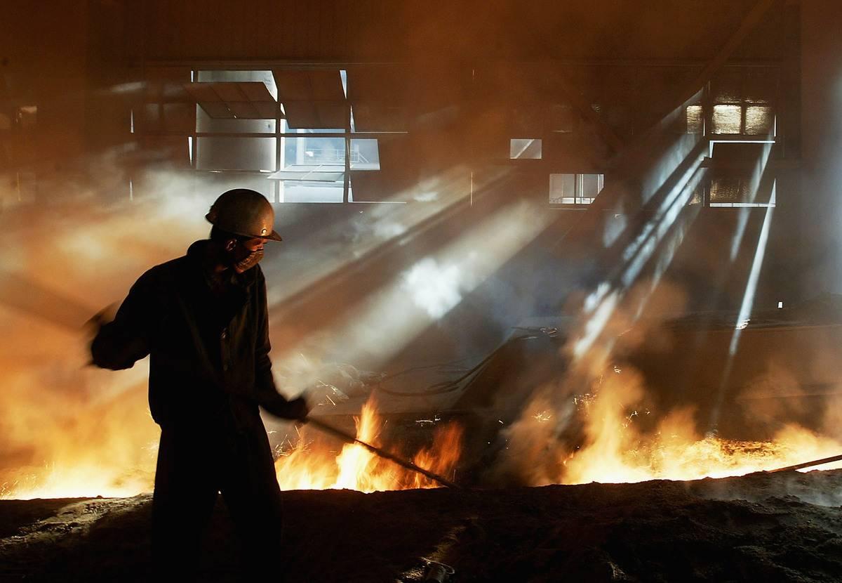 A steelworker work near fire in a steel mill.
