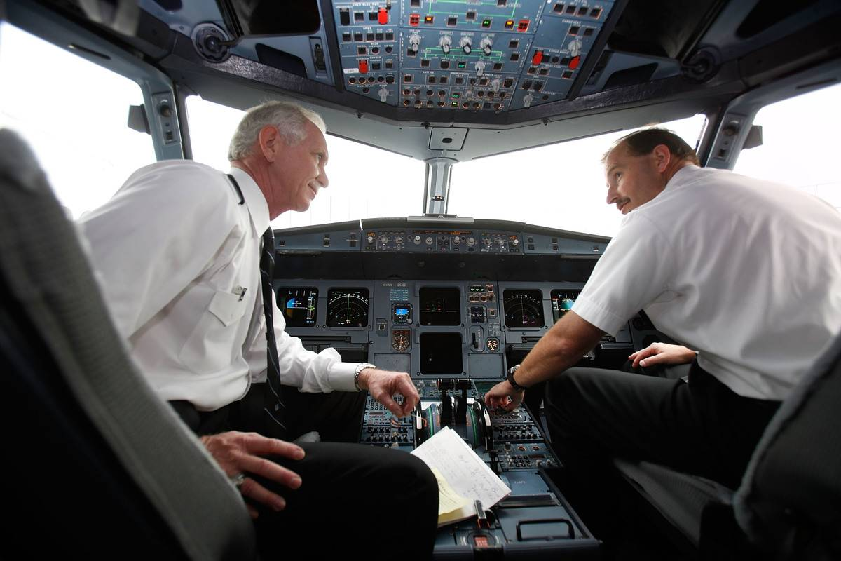 Two airline pilots talk to each other in the cockpit.