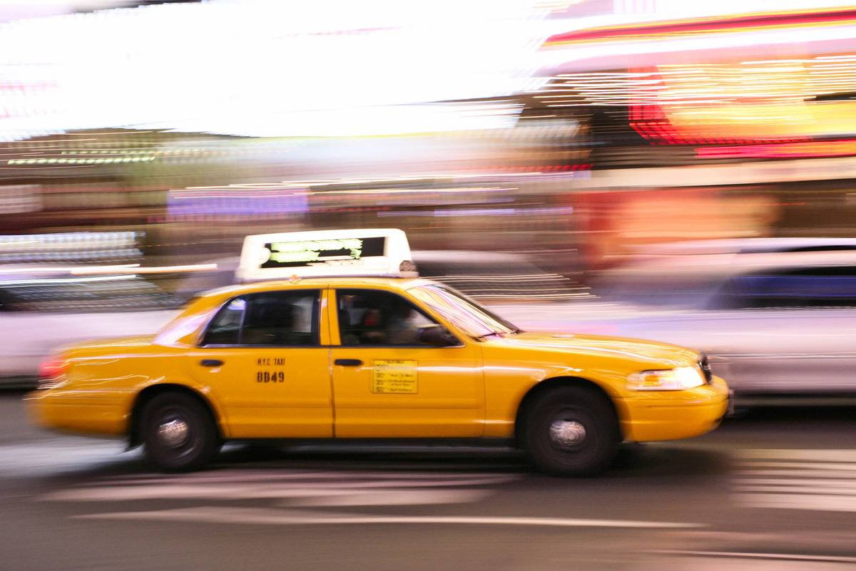 A taxi speeds through Times Square in New York City.
