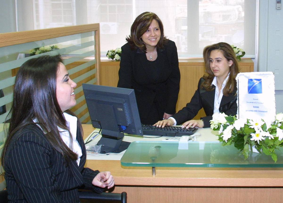 Financial advisors speak to a customer from behind their desk.