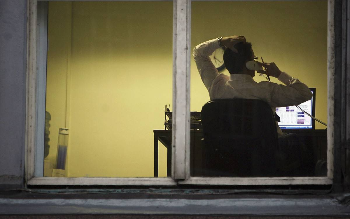 A compliance worker is seen talking on the phone through a window.