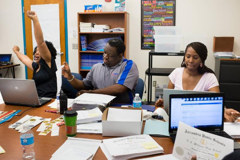 Three school counselors work at a long desk.