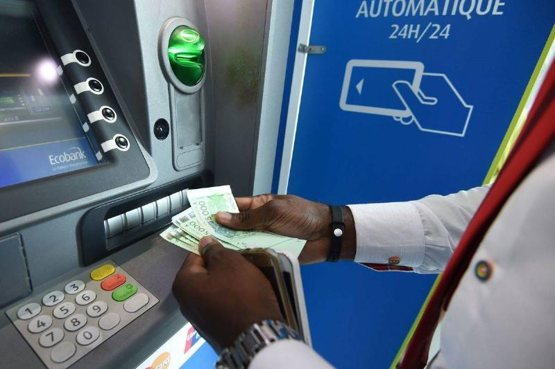 A well-dressed man takes money out of an ATM.