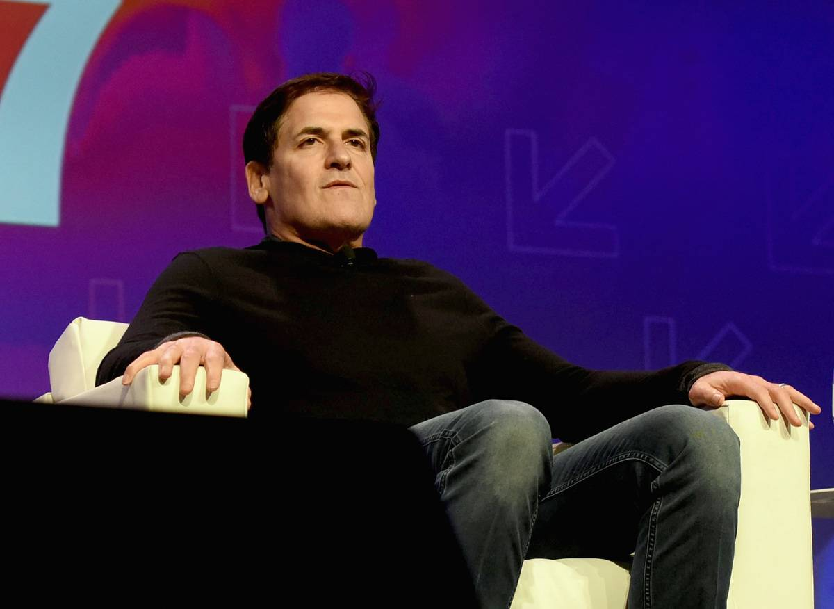 Mark Cuban sits in a chair onstage during a conference.