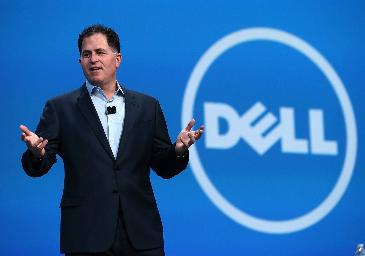 Michael Dell stands in front of a Dell logo while speaking during a conference.