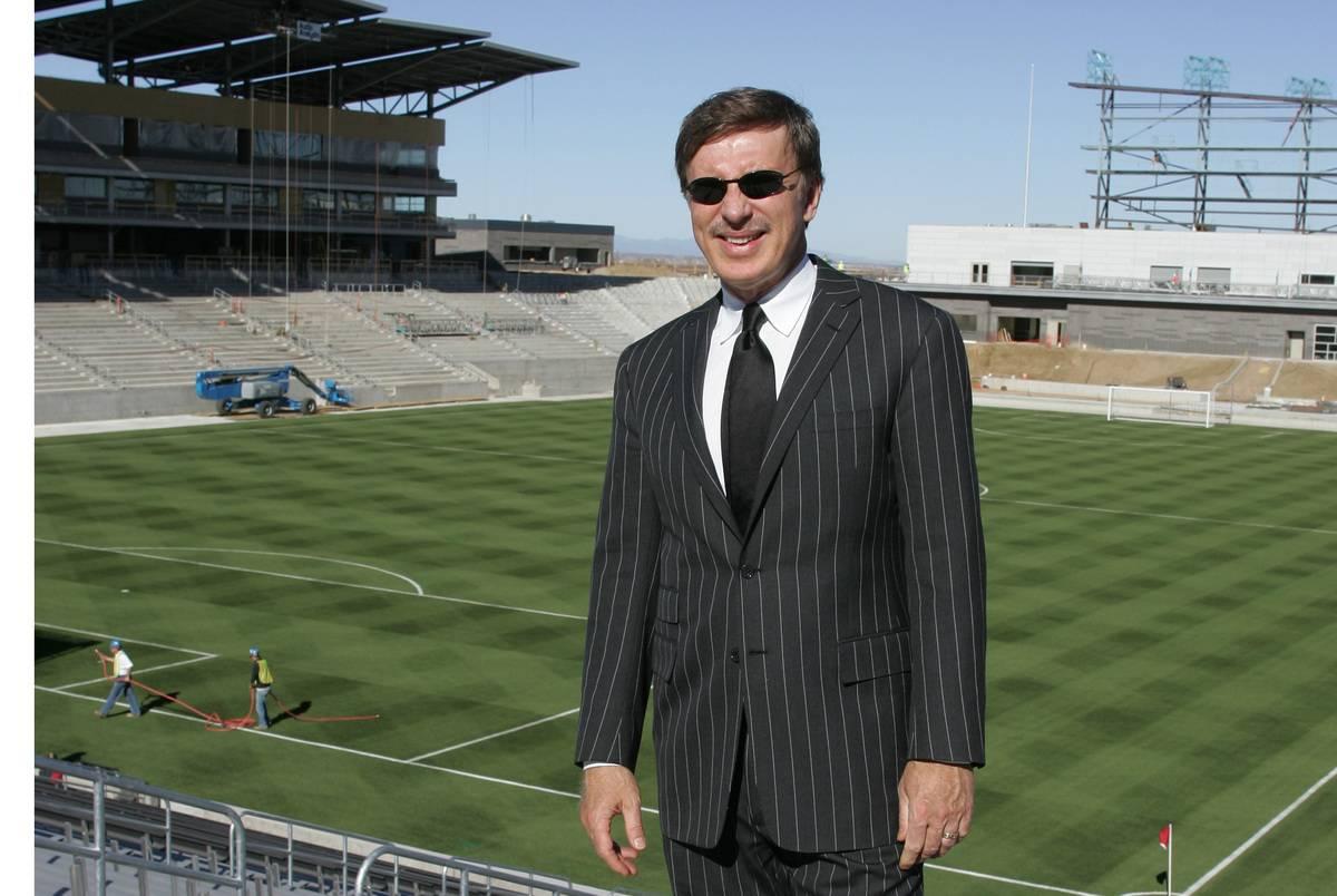 Stanley Kroenke stands in front of a soccer field.