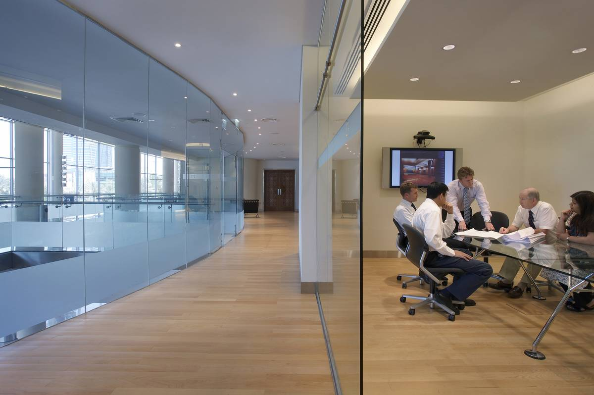 Multiple people sit around a business meeting.