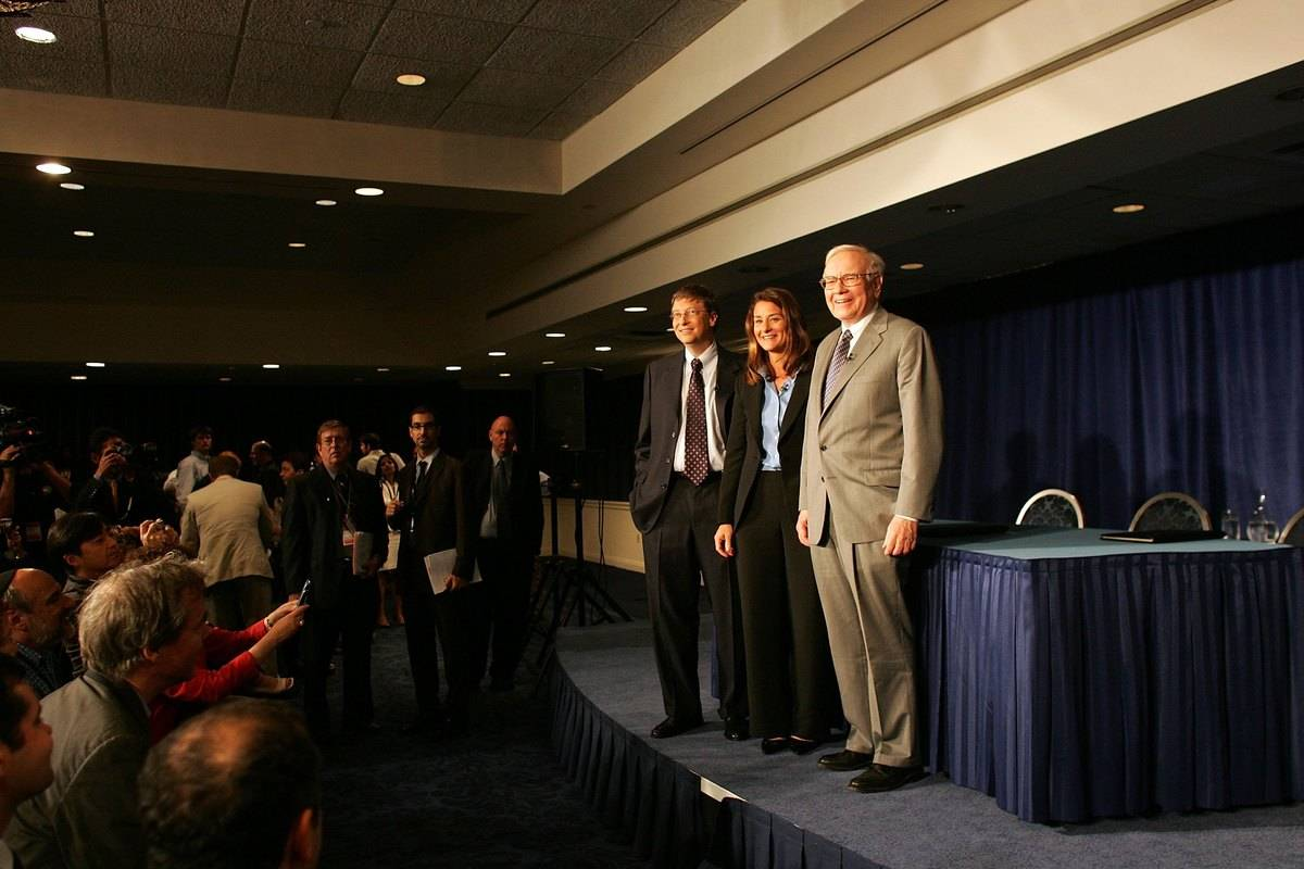 Warren Buffett stands next to Bill and Melinda Gates onstage during a charity event.