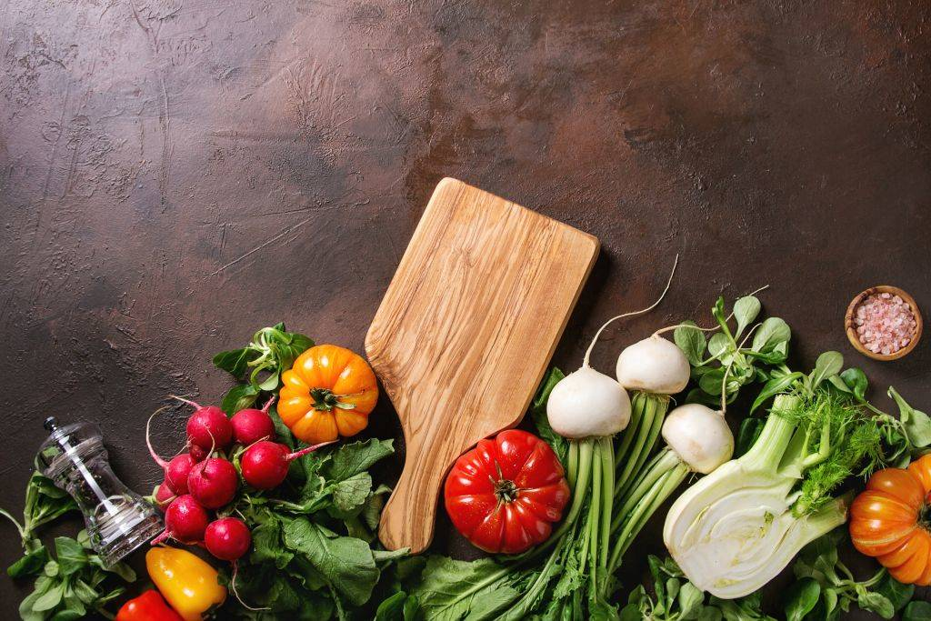 Variety of wet raw fresh organic colorful vegetables tomatoes, radish with leaves, fennel, paprika, salt, pepper, wooden chopping board for salad over dark brown texture background