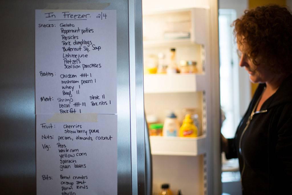 woman holding her fridge door open