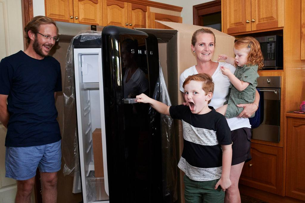 family standing with their new fridge