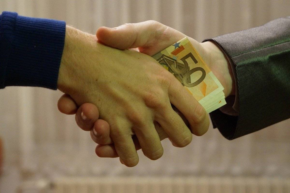 People shake hands while passing cash.