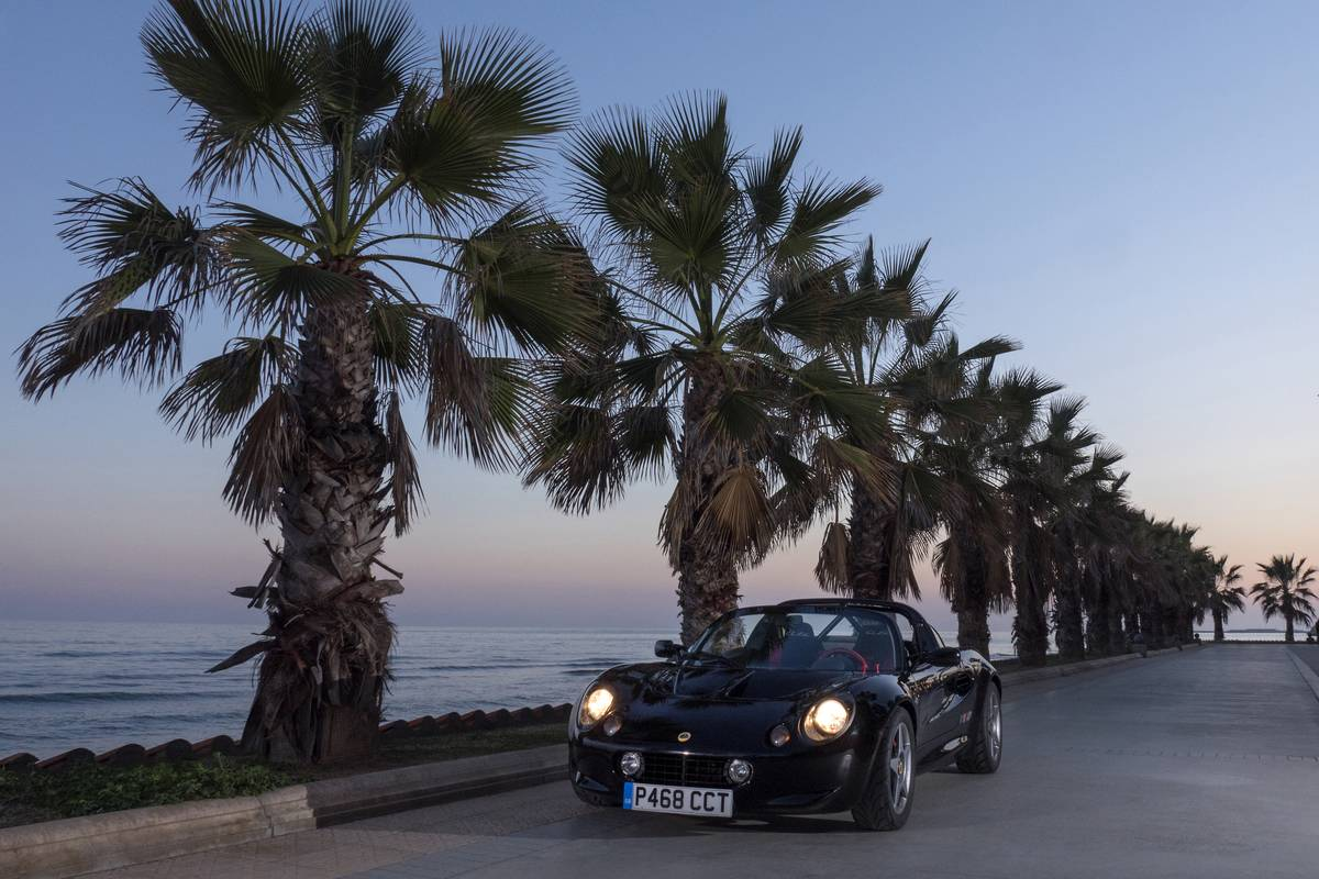 A 1997 Lotus Elise Sport drives by palm trees.