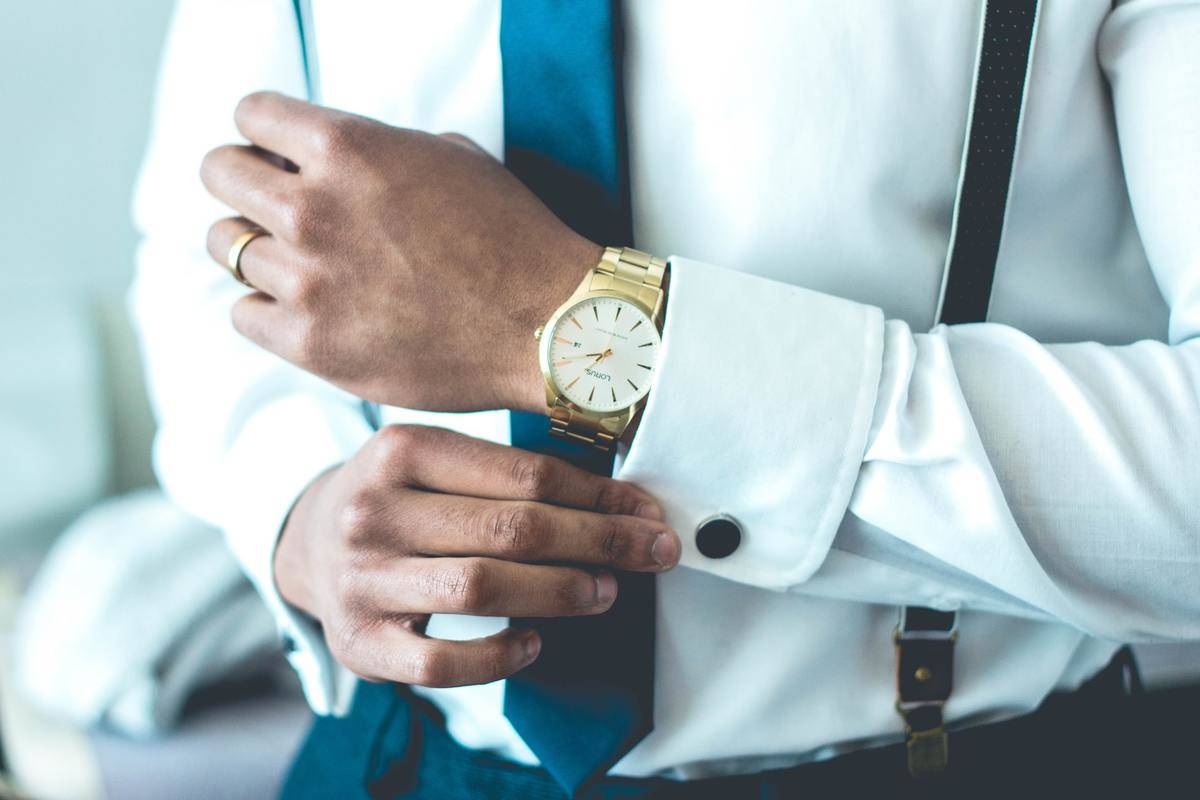 A man wearing a luxury watch adjusts the cuffs on his shirt.